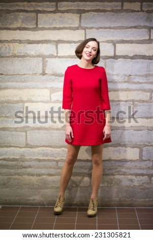 Young woman in hallway stand on brown floor plate - stock photo