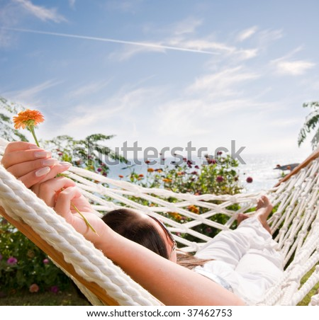Young woman in hammock, focus on the flower (shallow dof) - stock photo