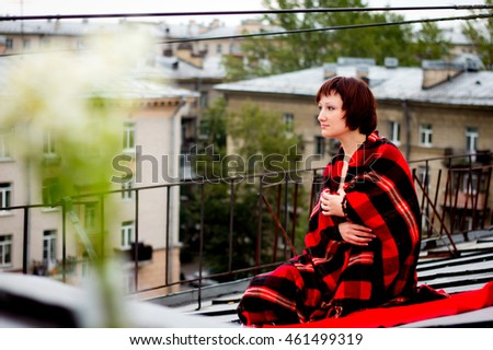Young woman in happy mood sitting and hiding red blanket in cage with  houses on the background on the morning. the happiness of pleasure and expectation concept