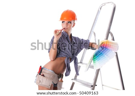 Young woman in hardhat with a color guide and paintbrush on a white background. - stock photo