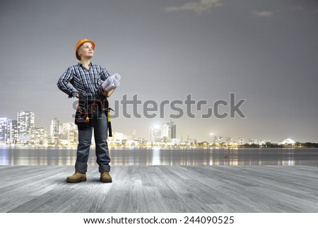 Young woman in hardhat with construction project in hands - stock photo