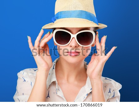 Young woman in hat and sunglasses , isolated on blue background - stock photo