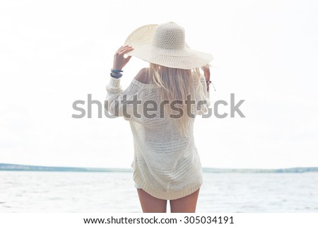 Young woman in hat and white pullover having rest by the sea