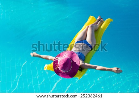 Young woman in hat enjoying a swimming pool - stock photo
