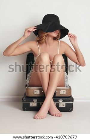 young woman in hat is sitting on old leather suitcase. Beauty and Fashion girl.summer travel concept - stock photo