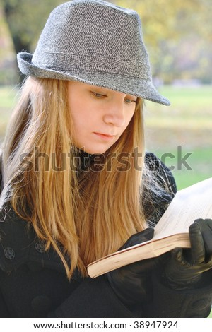 Young woman in hat reading book in autumn park closeup