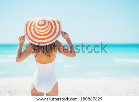 Young woman in hat standing on beach. rear view - stock photo