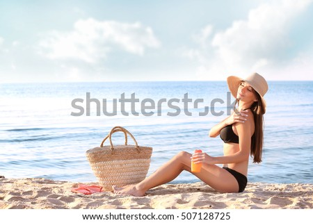 Young woman in hat sunbathing and using sunscreen on the sea background