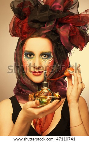 Young woman in hat with bows with vintage bottle of perfume in her hands - stock photo