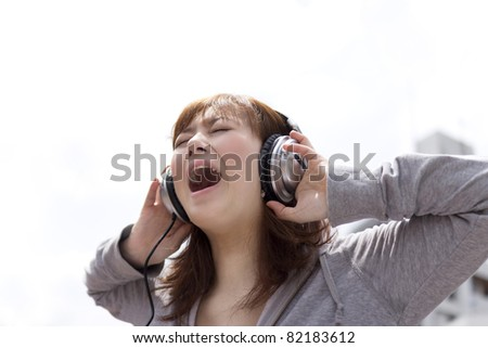 Young woman in headphone. Asian woman