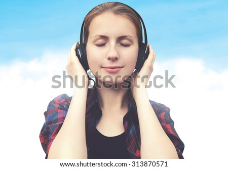 Young woman in headphones relaxes and listens to music over blue sky with clouds - stock photo