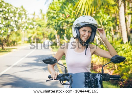 Young woman in helmet is sitting on motorbike