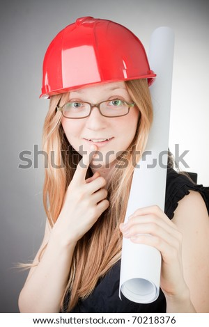Young woman in helmet with blueprint, with grey background - stock photo