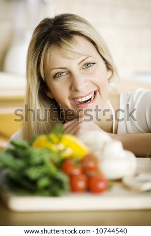 young woman in her kitchen, behind fresh ingredients - stock photo