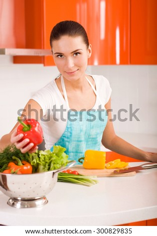 Young woman in her kitchen cutting vegetables - stock photo