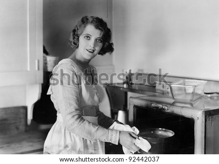 Young woman in her kitchen putting a pot into the oven