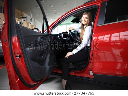 Young woman in her new car smiling - stock photo