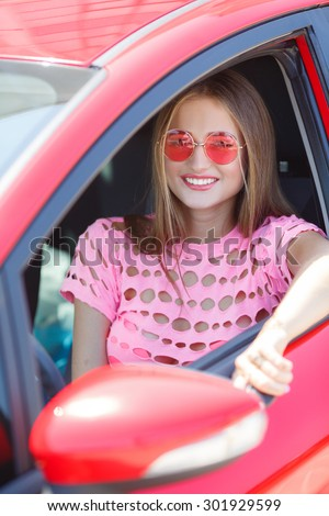 Young woman in her new car smiling. Woman Sitting In Car Getting Ready To Drive. car driver woman smiling showing new car keys and car.  - stock photo