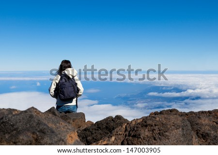 Young Woman in High Mountain Range wit a Sea of Clouds - stock photo