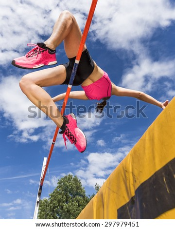 young woman in highjump in track and field - stock photo
