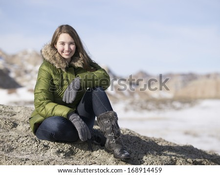 Young woman in Hilly Countryside or Badlands during Winter
