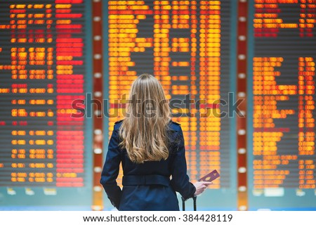 Young woman in international airport looking at the flight information board, checking her flight - stock photo
