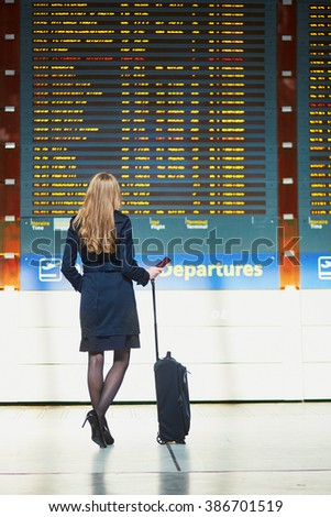 Young woman in international airport looking at the flight information board, holding passport in her hand, checking her flight - stock photo