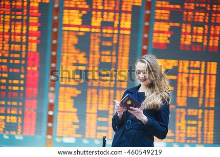 Young woman in international airport near the flight information board, checking her passport