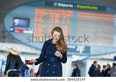 Young woman in international airport near the flight information board, checking her phone - stock photo