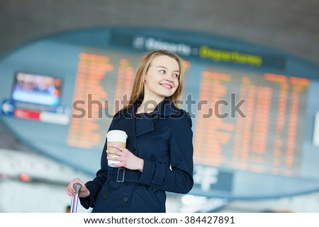 Young woman in international airport near the flight information board, with hot beverage to go