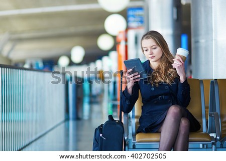 Young woman in international airport, reading and drinking coffee while waiting for her flight - stock photo
