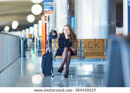Young woman in international airport, waiting for her flight and looking upset or worried. Missed, canceled or delayed flight concept