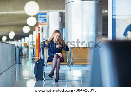 Young woman in international airport, waiting for her flight, checking her watch and looking upset or worried. Missed, canceled or delayed flight concept - stock photo