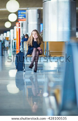 Young woman in international airport, waiting for her flight, looking upset or worried. Missed, canceled or delayed flight concept - stock photo