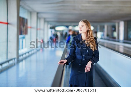 Young woman in international airport walking along the travelator - stock photo