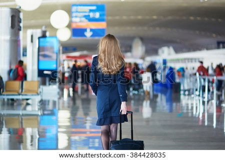 Young woman in international airport, walking with her luggage, back view. Flight attendant going to meet her crew