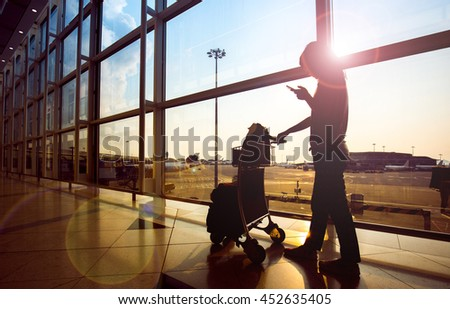 Young woman in international airport with luggage trolley - stock photo