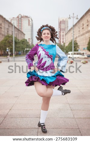 Young woman in irish dance dress and wig dancing outdoor - stock photo