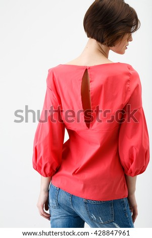 Young woman in jeans and pink blouse on white background