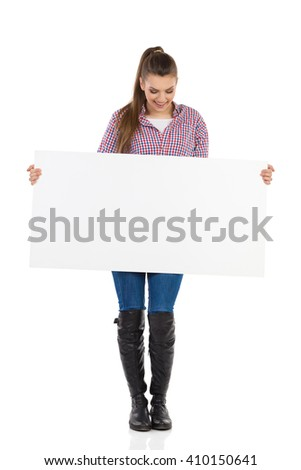 Young woman in jeans, black boots and lumberjack shirt standing, holding white placard and reading. Full length studio shot isolated on white. - stock photo