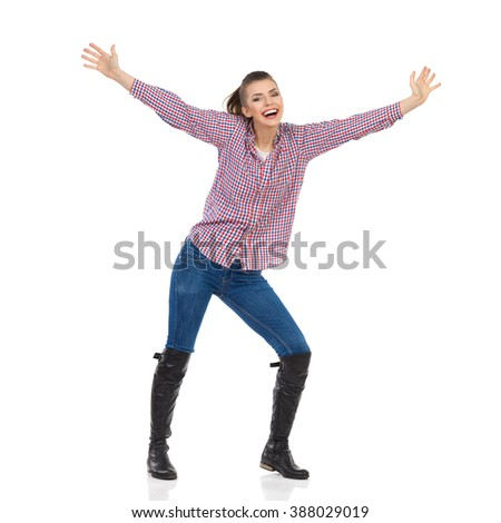 Young woman in jeans, black boots and lumberjack shirt standing with arms outstretched and shouting. Full length studio shot isolated on white.