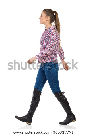 Young woman in jeans, black boots and lumberjack shirt walking. Side view, full length studio shot isolated on white.