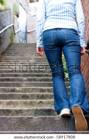 young woman in jeans going up steep stairs - stock photo