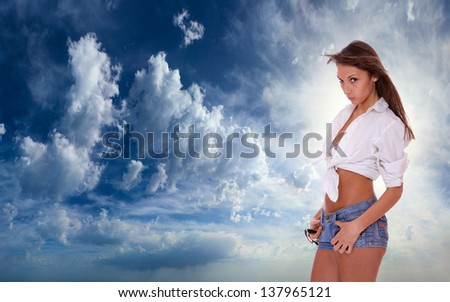 Young woman in jeans shorts  standing on blue cloudy sky backgroound