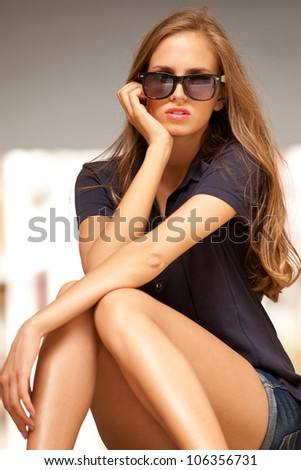 young woman in jeans shorts wearing sunglasses sit on stairs outdoor shot summer day - stock photo