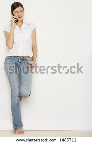 Young woman in jeans talking on cell phone - stock photo