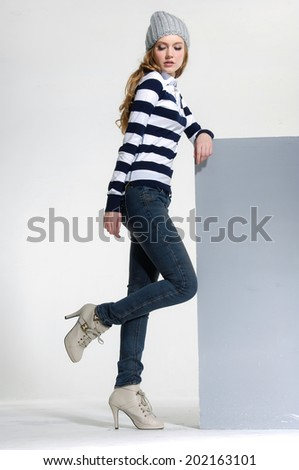 young woman in jeans with beret with wooden cube posing - stock photo