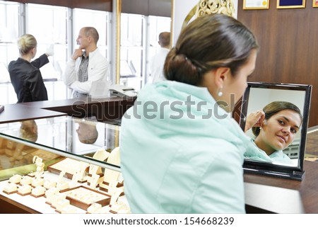 Young woman in jewelry boutique shop choosing earring