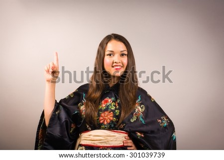 young woman in kimono showing index finger with idea