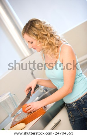 young woman in kitchen cutting vegetables - stock photo